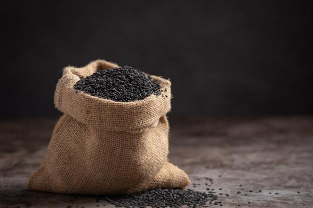 Schwarzer sesam im sack auf dunklem hintergrund