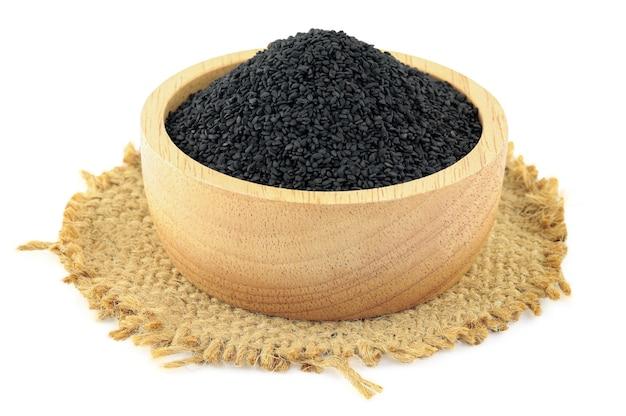 Schwarzer sesam in einer hölzernen schüssel auf sack lokalisiert auf weißem hintergrund mit beschneidungspfad.