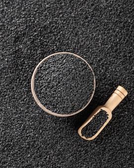Schwarzer sesam in einer keramikschale und einem holzlöffel, selektiver fokus, draufsicht