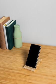 Schwarzer smartphone auf hölzernem stand