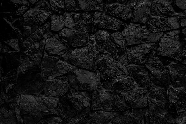 Schwarzer steinmauerhintergrund.