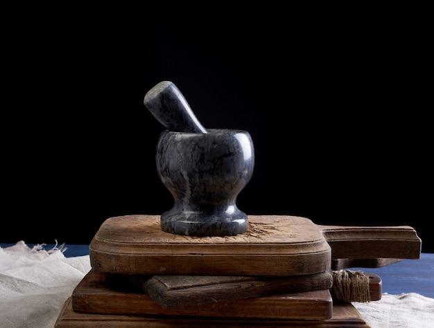 Schwarzer steinmörser mit stößel zum mahlen von gewürzen und kräutern auf einem braunen holzbrett