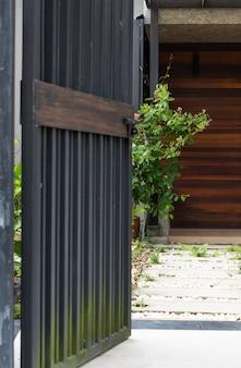 Schwarzer stell tür-zauneingang zum haus mit gehweg des betonblocks und der weißen steine