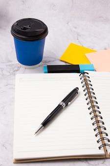 Schwarzer stift auf offenem buch, leere notizbuchseite, blauer textmarker, haftnotiz und blaue tasse kaffee auf weißem marmortisch. schreibtisch aus marmor. schablone. hintergrund.