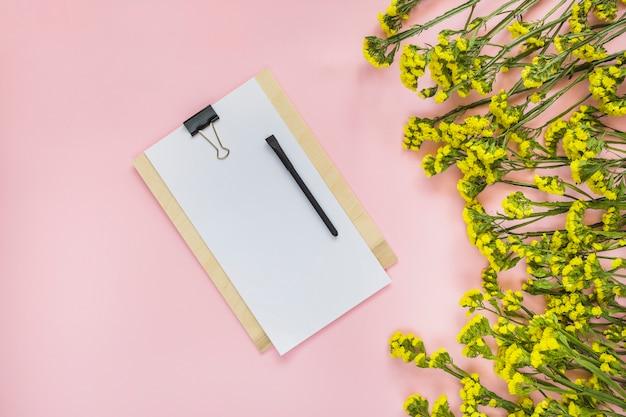 Schwarzer stift auf papier über hölzernem klemmbrett und gelben blumen gegen rosa hintergrund