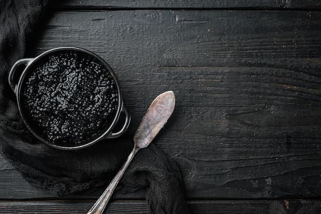 Schwarzer störkaviar in der schüssel auf schwarzem holztisch