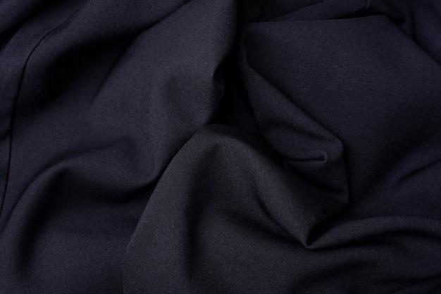 Schwarzer stoff faltet den hintergrund. sicht von oben. konzeptverkauf am black friday