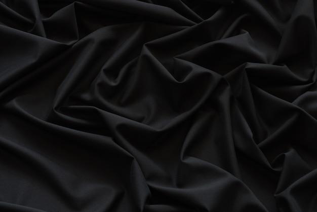 Schwarzer stoff hintergrund und textur, gerillt aus schwarzem stoff abstrakt