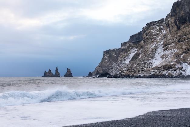 Schwarzer strandfelsen und -wellen nahe dem vik während des wintersonnenuntergangs