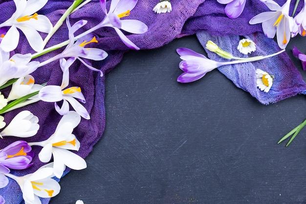 Schwarzer strukturierter hintergrund mit lila gefärbtem stoff und frühlingsblumen