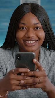 Schwarzer student, der in die kamera schaut, während er in den sozialen medien surft und nachrichten mit freunden auf einem modernen smartphone eingibt. junge frau sitzt am schreibtisch im wohnzimmer und teilt gruppengespräche