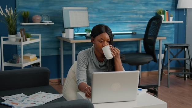 Schwarzer student trinkt kaffee und tippt social-media-artikel, die das webinar zur vorlesungskommunikation auf einem laptop im wohnzimmer durchsuchen