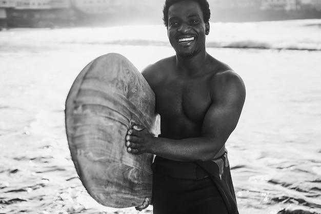 Schwarzer surfermann, der weinlese-surfbrett am strand am sommersonnenuntergang hält - fokus auf gesicht