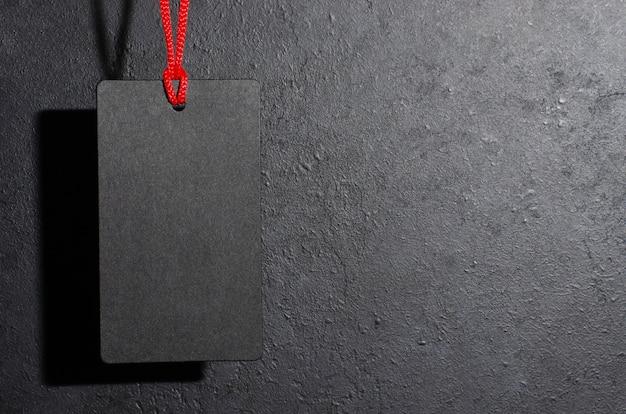Schwarzer tag, der auf schwarzem hintergrund hängt