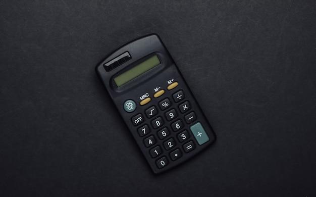 Schwarzer taschenrechner auf einem schwarzen.
