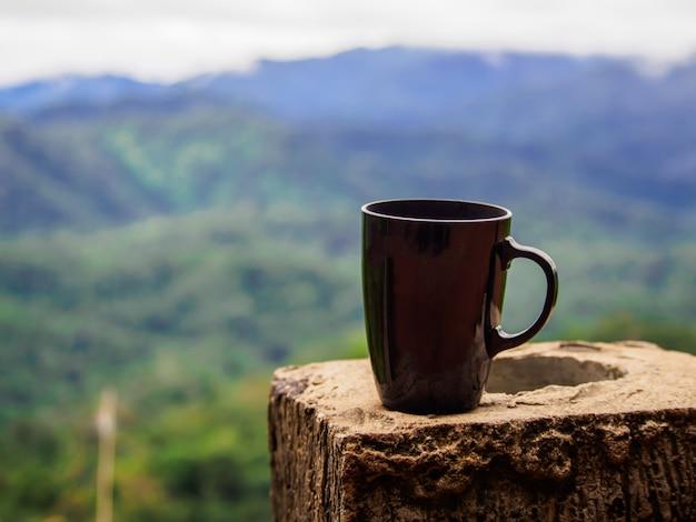 Schwarzer tasse kaffee auf der zementsäule auf unschärfegebirgs- und -waldhintergrund morgens