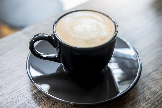 Schwarzer tasse kaffee mit dem milchschaum, der auf altem holztisch so köstlich ist