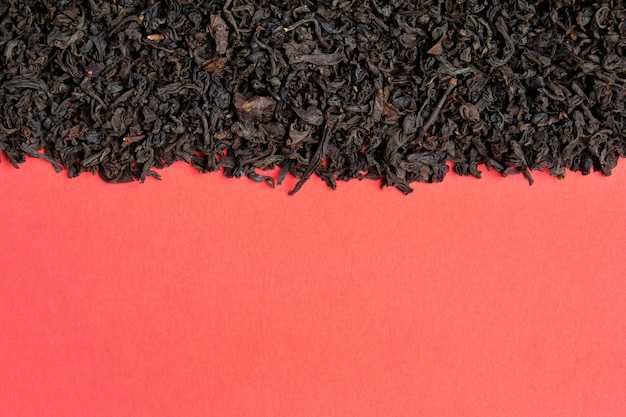 Schwarzer tee auf rotem grund. draufsicht.