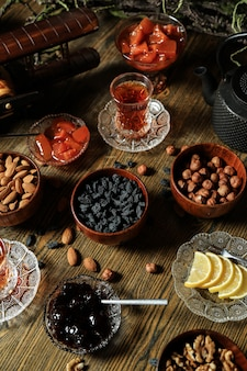 Schwarzer tee im armudu-glas mit verschiedenen nüssen und marmelade