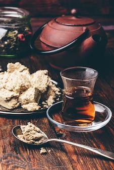 Schwarzer tee in armudu-glas und löffel halva