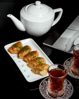 Schwarzer tee in armudu mit türkischem pakhlava