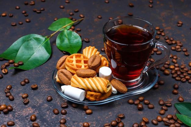 Schwarzer tee in der glasschale mit süßigkeiten auf dunkelheit