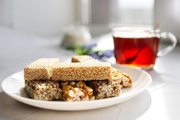Schwarzer tee in einem glasbecher, ein teller mit gesunden handgemachten orientalischen süßigkeiten, nüssen, samen und sesam in karamellzucker. sonniger morgen, teeparty.