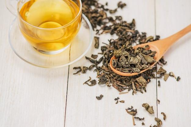 Schwarzer tee in einer glastasse und teeblätter in holzlöffel auf schwarzem steinhintergrund.