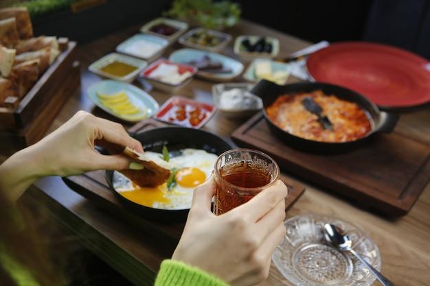 Schwarzer tee in glas und frühstücksset nahaufnahme