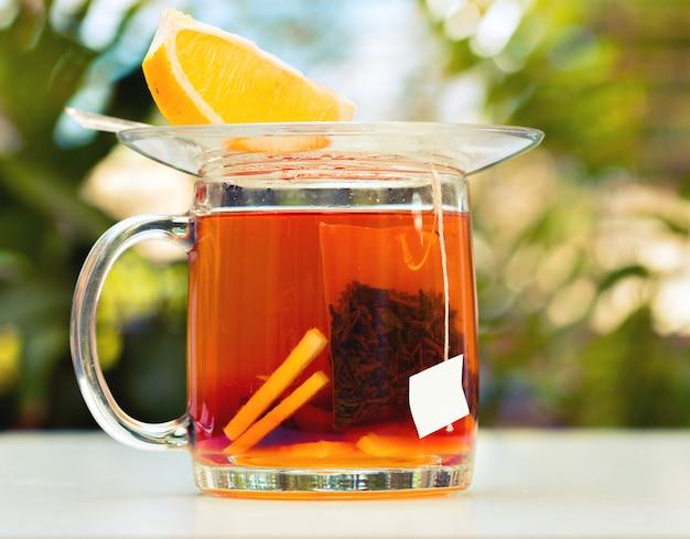 Schwarzer tee mit einer zitronenscheibe in einem glaskrug