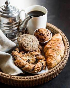Schwarzer tee mit gebackenem essen auf korbtablett
