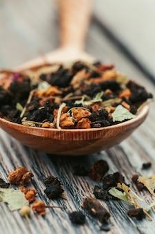 Schwarzer tee mit kräutern auf einem hölzernen brett
