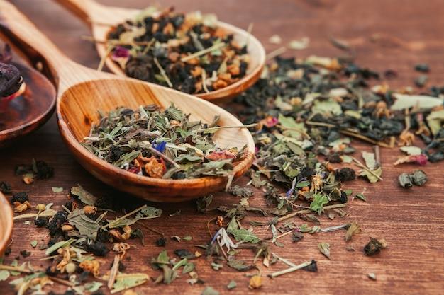 Schwarzer tee mit kräutern in den hölzernen löffeln auf einem hölzernen brett