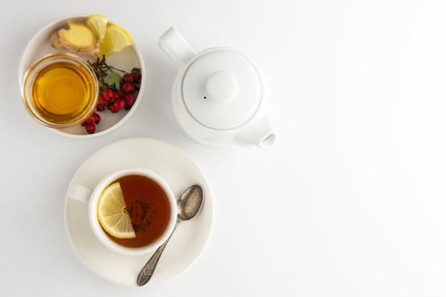 Schwarzer tee mit lemonnd honig auf weiß.