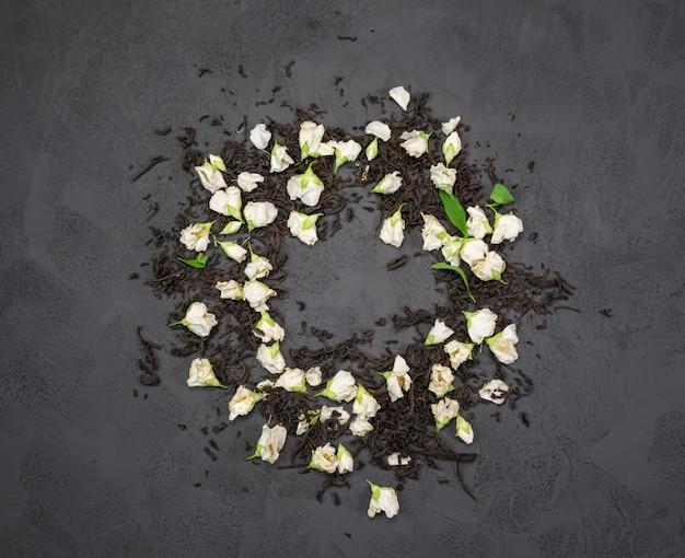 Schwarzer tee mit trockenem jasmin blüht auf einer schwarzen beschaffenheit