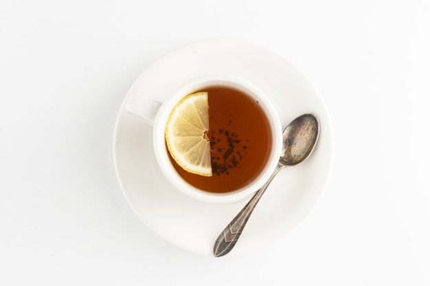 Schwarzer tee mit zitrone und honig auf einem weiß. heiße teeschale lokalisiert, draufsichtebenenlage. flach liegen. herbst-, herbst- oder wintergetränk. copyspace.