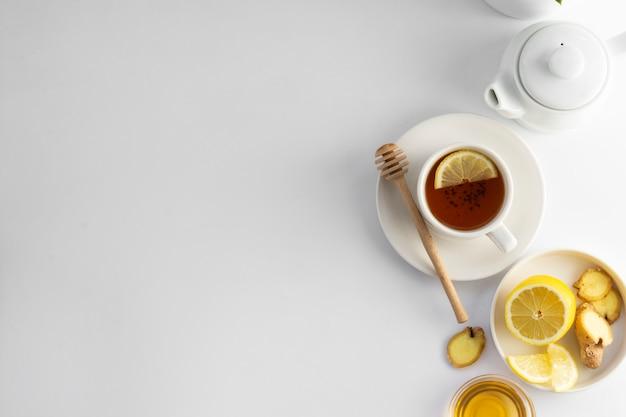 Schwarzer tee mit zitrone und honig auf einem weißen hintergrund