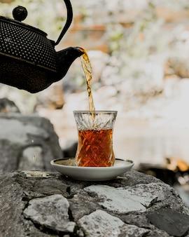 Schwarzer tee serviert in traditionellem armudu glas