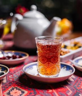Schwarzer tee von der seite in einem birnenförmigen glas auf einer untertasse mit süßigkeiten und teekanne auf dem tisch