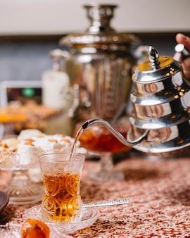 Schwarzer tee wird aus stahlteekanne in kristallarmudu-glas gegossen
