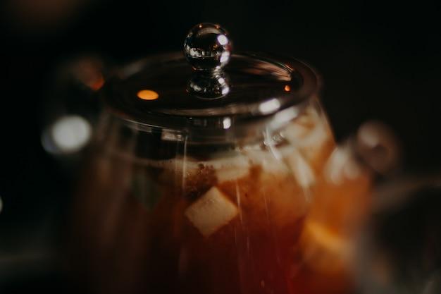 Schwarzer teekannen-, schüssel- und hibiscustee auf farbholztisch