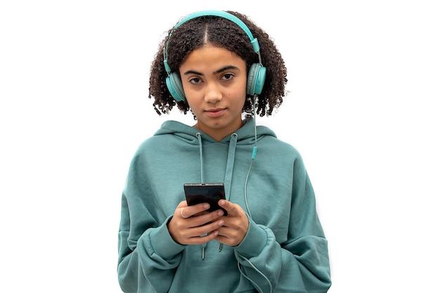 Schwarzer teenager, der kamera beim verwenden des smartphones betrachtet und musik lokalisiert auf weißem hintergrund hört