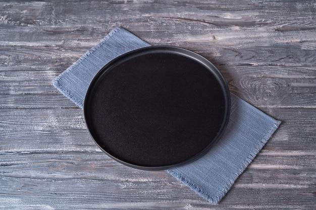 Schwarzer teller auf blauer serviette auf einem grauen holztisch