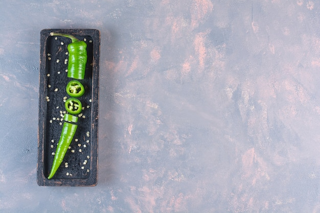 Schwarzer teller mit frischem grünem chilipfeffer auf steinoberfläche
