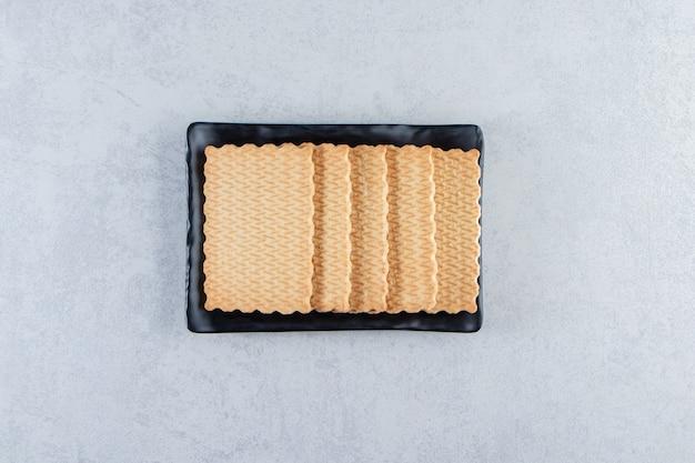 Schwarzer teller mit leckeren keksen auf stein.