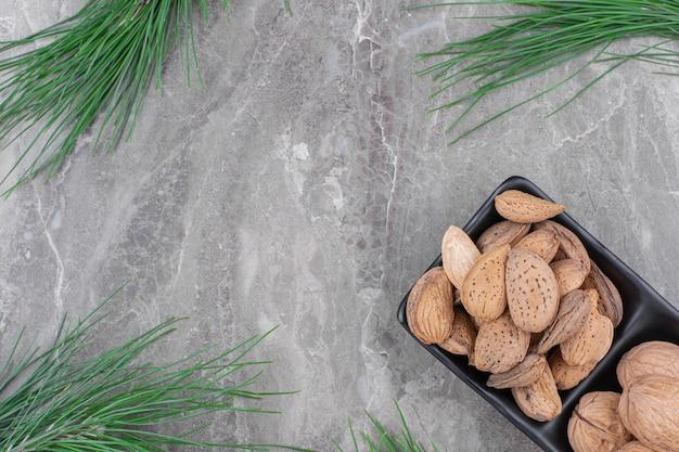 Schwarzer teller mit organisch geschälten mandeln auf marmoroberfläche.