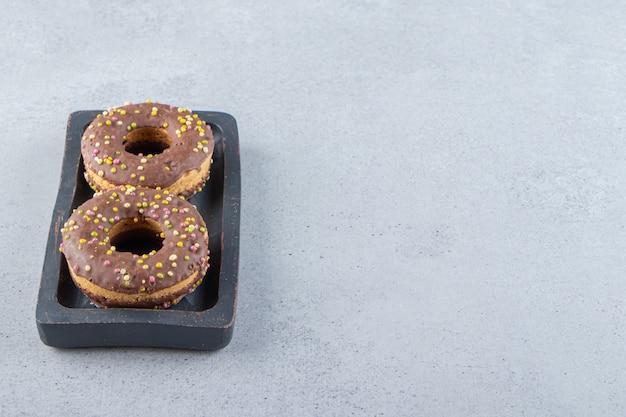 Schwarzer teller mit schokoladenkrapfen auf steinhintergrund. foto in hoher qualität