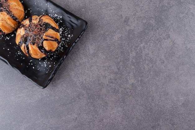 Schwarzer teller mit schokoladenprofiteroles auf steintisch gelegt.