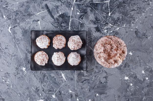 Schwarzer teller mit süßen cremigen cupcakes und einem glas kaffee auf marmoroberfläche.