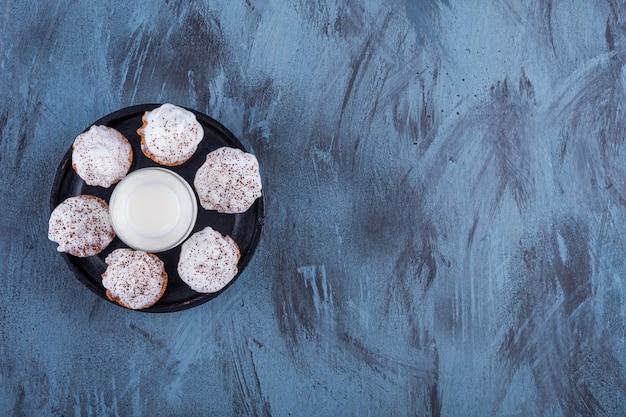 Schwarzer teller mit süßen cremigen cupcakes und einem glas milch auf marmor.
